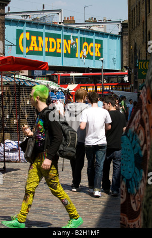 London , punk young man or boy or male or adult with green hair and shoes in market by railway bridge at Camden - Stock Photo