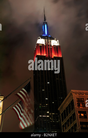 Empire State building in New York City at night time with American flags in foreground red white and blue lights - Stock Photo