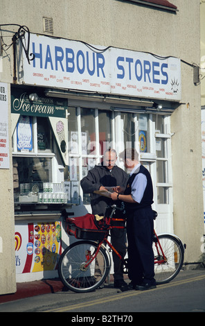 A postman delivering letters in front of a shop, Lyme Regis, Dorset, England - Stock Photo