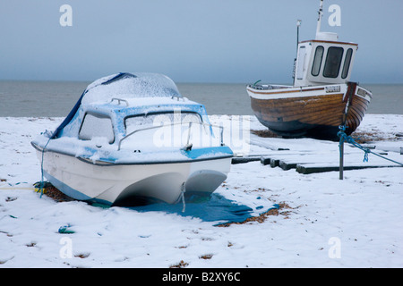Boats on the beach covered in snow in Deal Kent - Stock Photo