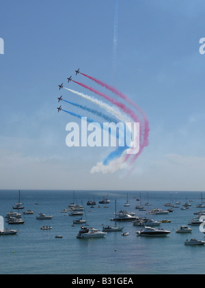 RAF Red Arrows aerial display team perform over Swanage Bay as part of the opening of Swanage Carnival Week, 27th - Stock Photo