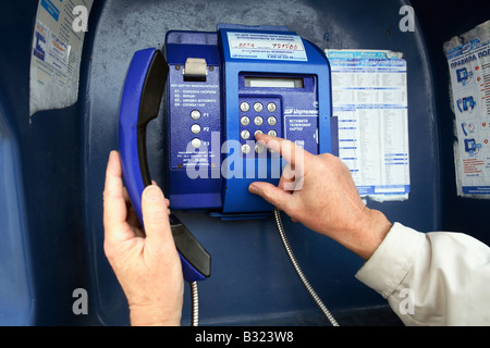 Man dialing a telephone number at a public phone booth, Yalta, Ukraine - Stock Photo