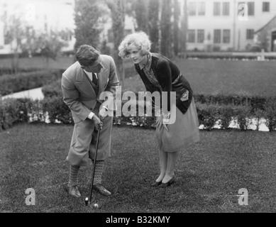 Man talking to woman while golfing - Stock Photo