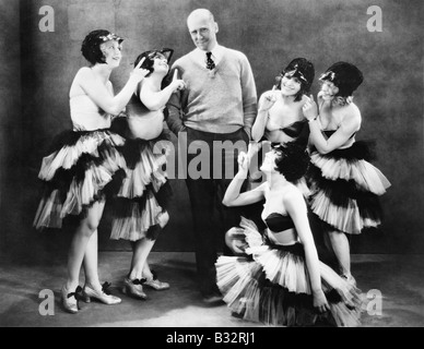 Five young women dancing around a man - Stock Photo