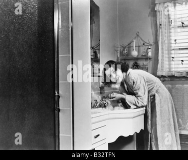 Profile of a young woman washing her hands in the bathroom sink - Stock Photo