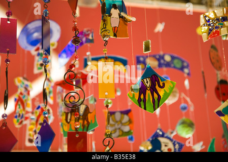 SPAIN Barcelona Colorful wind chimes with painted designs and shaped metal hanging on display in gift shop - Stock Photo