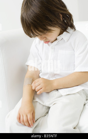 Little boy picking at adhesive bandage on his arm, head down - Stock Photo