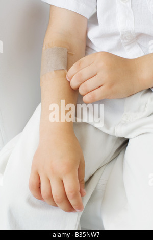 Little boy picking at adhesive bandage on his arm, cropped view - Stock Photo