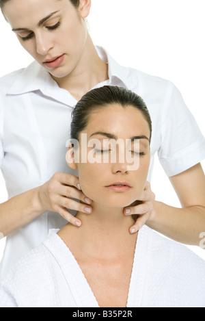 Massage therapist giving woman neck massage, eyes closed - Stock Photo