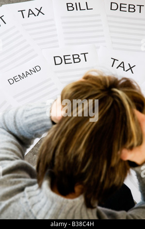Woman with head in hands worrying about household debt and bills - Stock Photo