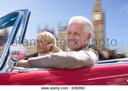 Couple driving in red convertible - Stock Photo