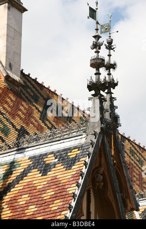 Superb Burgundian roof tiles and weather vane on a dormer of the Hospice Hotel-Dieu in Beaune Burgundy France Europe - Stock Photo