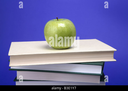 A green apple on a pile of books with a blue background - Stock Photo