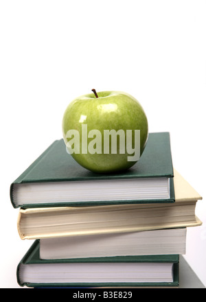 A shiny green apple on a pile of text books - Stock Photo