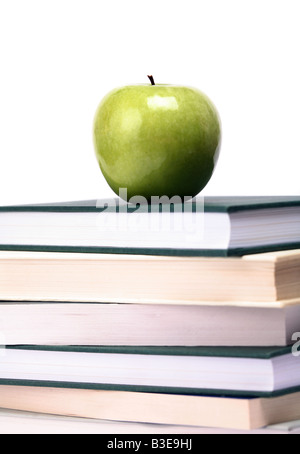 An apple on top of a pile of books white background - Stock Photo