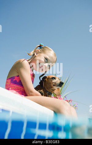 Girl and pet dachshund by pool - Stock Photo