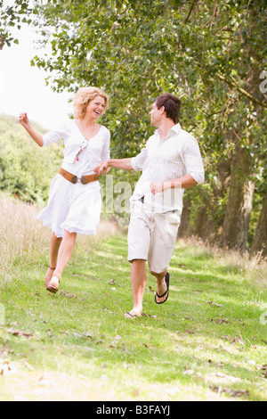 Couple running on path holding hands and smiling - Stock Photo
