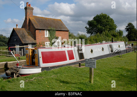 Traditional narrowboat passing through Triggs Lock on the River Wey Navigation near Woking, Surrey, England - Stock Photo