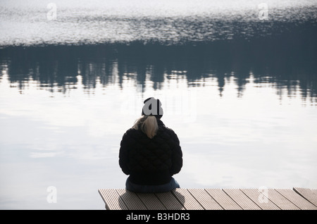 solitary woman sitting in front of a lake in winter. - Stock Photo