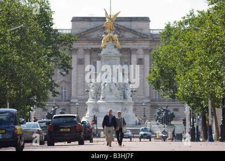 A couple walk down the centre of the Mall away from the Victoria Memorial and the Queen's Buckingham Palace in London - Stock Photo