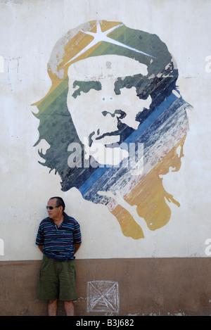 Elderly man near a wall painting of Ernesto Che Guevara in Havana Cuba April 2007 - Stock Photo