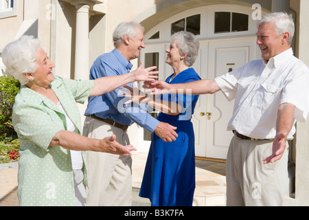 Two senior couples greeting each other with open arms - Stock Photo