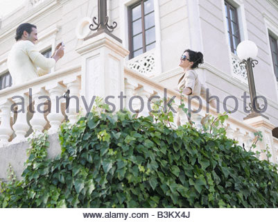 Couple taking pictures on balcony - Stock Photo