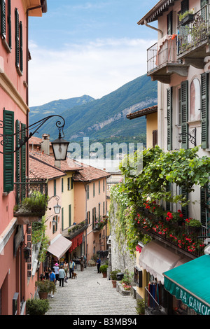 Narrow street in the town centre looking downhill towards the lake, Bellagio, Lake Como, Lombardy, Italy - Stock Photo