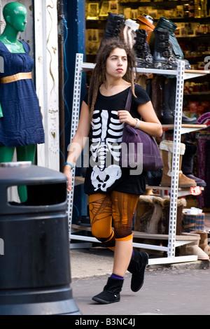 London Camden Lock Market pretty young female teenage girl brunette t shirt skeleton torn tights purple shoulder - Stock Photo