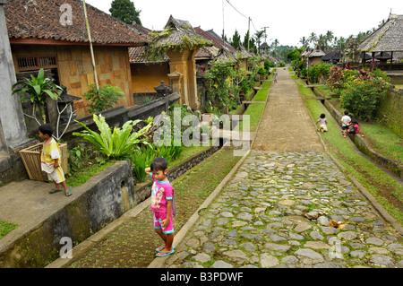 Traditional village, main street, children in Bangli, Bali, Indonesia - Stock Photo