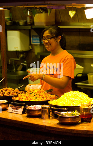 London , Camden Stables & Lock Market , pretty smiling girl in glasses serves Halal street food at Indian fast food - Stock Photo