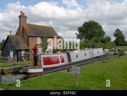 Man on stern of traditional narrowboat passing through Triggs Lock on the River Wey Navigation, near Woking, Surrey, - Stock Photo