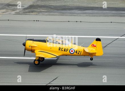 Old trainer plane North American AT-6 Texan taking off on the runway during an airshow in Alaska - Stock Photo