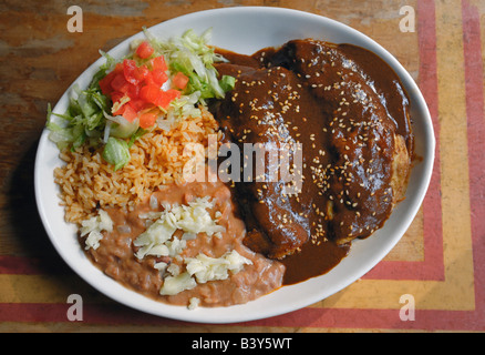 Chicken enchiladas with a Mole Poblano sauce and rice and beans. - Stock Photo