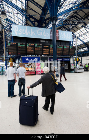 People waiting in front of the timetable information boards on the concourse area of brighton station east sussex - Stock Photo