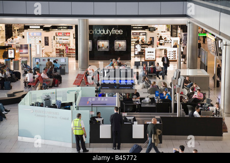 People in London Heathrow Airport British Airways departures lounge inside Terminal 5 building with duty free shops - Stock Photo