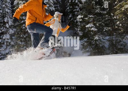 Austria, Salzburger Land, Altenmarkt-Zauchensee, Young couple running in snow - Stock Photo