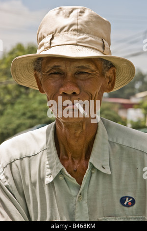 Cambodian man wearing a hat and smoking a cigarette - Stock Photo