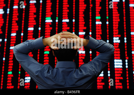 Stock Trader Stood in Front of a Large Display of Stock Prices - Stock Photo