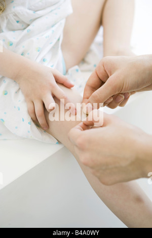 Woman putting adhesive bandage on little girl's knee, cropped view - Stock Photo