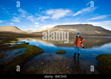 Person standing at the edge of a lake, Nunavut, Canada - Stock Photo