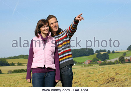 young couple walking through the landscape - Stock Photo
