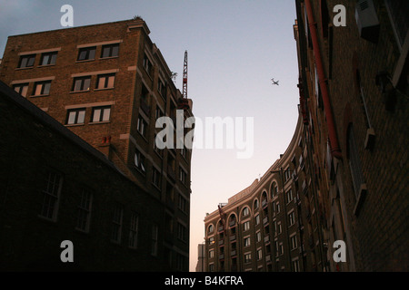 A Plane flies over Gun Wharf in Wapping, London England UK - Stock Photo