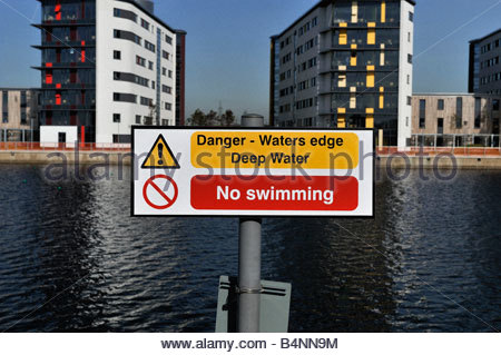 A sign warning about deep water and stating that no swimming is allowed - Stock Photo