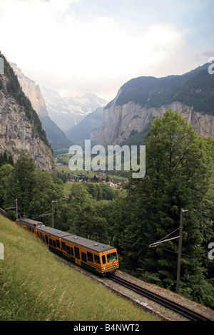 The Lauterbrunnen Valley with the Lauterbrunnen to Wengen train in the Jungfrau Region, southern Switzerland. - Stock Photo