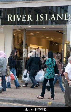 shoppers outside the River Island clothes store Preston city centre Lancashire England UK - Stock Photo