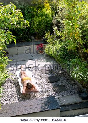 Young woman in bikini in garden - Stock Photo