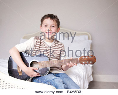 Young boy sitting on bed playing guitar - Stock Photo