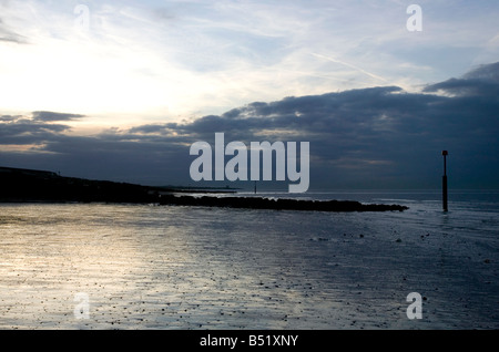 Silhouette of stone breakwater on a beach Minnis Bay near margate Kent - Stock Photo