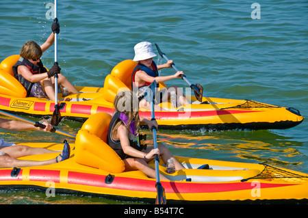boys girl kayaking racing race bright color yellow PVC inflatable sit-on-top kayaks - Stock Photo